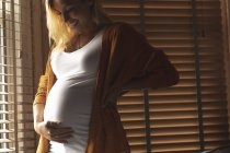 Smiling pregnant woman touching her belly near the window — Stock Photo