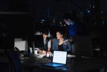 Tre genti di affari che lavora al computer portatile in ufficio durante le ore notturne — Foto stock