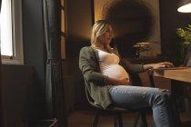 Беременная женщина использует ноутбук дома — стоковое фото
