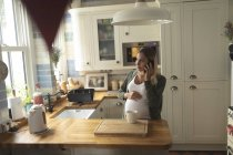 Pregnant woman talking on the phone in kitchen at home — Stock Photo