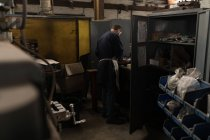 Rear view of blacksmith working in workshop — Stock Photo