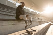 Disabled athlete listening music on mobile phone at sports venue — Stock Photo