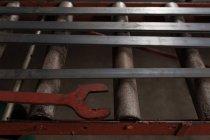Primer plano de varilla de Metal plana y llave en taller - foto de stock