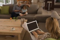 Woman using laptop while grandmother and granddaughter using mobile phone and digital tablet at home — Stock Photo
