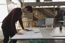 Ejecutivo masculino con tableta digital mientras se trabaja en planos en oficina - foto de stock