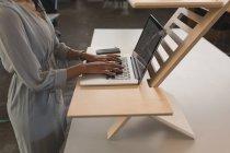 Середине раздел женского исполнительной работы на ноутбуке в офисе — стоковое фото