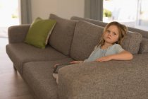 Girl relaxing on a sofa in living room at home — Stock Photo