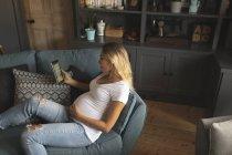 Femme enceinte lisant une tablette numérique sur le canapé à la maison — Photo de stock