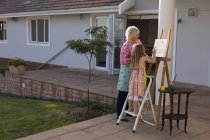 Granddaughter and grandmother painting on canvas in the porch — Stock Photo