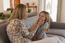 Мама играет со своей дочерью в гостиной на дому — стоковое фото