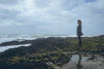 Thoughtful redhead woman standing in beach on rocks. — Stock Photo