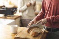 Cortada a visão do homem corte pão na cozinha em casa — Fotografia de Stock