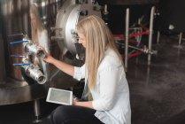 Молода жінка працівник вивчення лікеро-горілчаний завод танк заводі — стокове фото