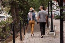 Задній вид пара ходіння по тротуару в місті — стокове фото