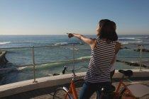 Молода жінка з велосипеда, стоячи на набережній і вказують на море біля пляжу — стокове фото