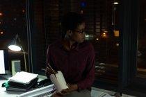 Esecutivo femminile che ha cibo in ufficio di notte — Foto stock