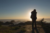 Силуэт пары, обнимающей друг друга на пляже на закате — стоковое фото