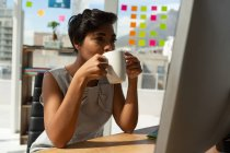 Female business executive having coffee while working in office. — Stock Photo