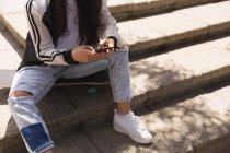 Sección baja de skater mujer con teléfono móvil en la ciudad de - foto de stock