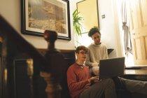 Пара взаимодействует друг с другом во время использования ноутбука дома — стоковое фото