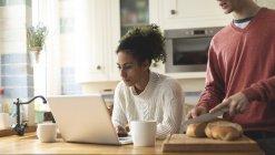 Mulher usando laptop enquanto fatia de corte homem de pão em casa — Fotografia de Stock