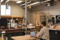Side view of craftsman using laptop in workshop — Stock Photo