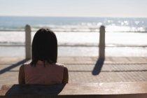 Вид сзади на женщину, сидящую на набережной возле пляжа — стоковое фото