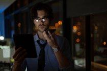 Мужчина руководитель разговаривает по мобильному телефону во время использования цифрового планшета в офисе ночью — стоковое фото