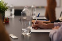 Cropped view of female executive writing on notepad in office — Stock Photo