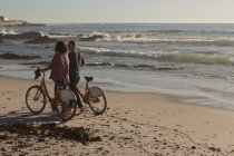 Couple with bicycles walking on beach in soft light — Stock Photo
