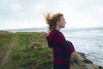 Ragionevole rossa donna in piedi con le braccia incrociate in spiaggia . — Foto stock