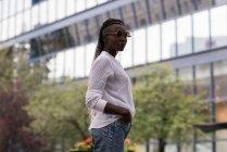 Mulher jovem na moda em óculos de sol de pé na cidade — Fotografia de Stock