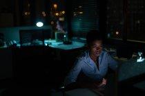 Жіночий виконавчий працює на столі в офісі вночі — стокове фото