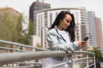 Jovem morena bonita usando telefone celular na cidade — Fotografia de Stock