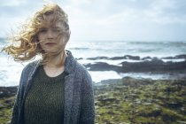 Portrait of redhead woman standing in windy beach. — Stock Photo