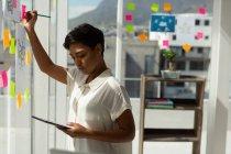 Führungskräfte schreiben auf Haftnotiz, während sie im Büro digitales Tablet verwenden. — Stockfoto