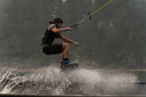 Jeune athlète wakeboard en rivière au crépuscule — Photo de stock