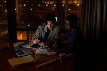 Ejecutivos discutiendo sobre tableta digital en la oficina por la noche - foto de stock