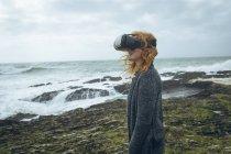 Рыжая женщина с гарнитурой виртуальной реальности на пляже . — стоковое фото