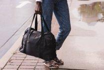 Close-up of woman with handbag standing on sidewalk — Stock Photo