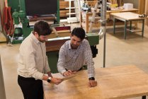Two craftsmen discussing over digital tablet in workshop — Stock Photo