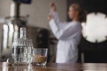 Nahaufnahme von Brauereiflasche und Weizenkorn im Glas mit Arbeiterinnen im Hintergrund — Stockfoto