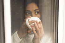 Femme réfléchie prenant un café à la maison — Photo de stock