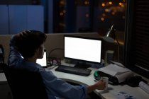 Male executive working at desk in office at night — Stock Photo