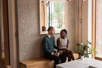 Casal jovem interagindo uns com os outros no café — Fotografia de Stock