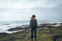 Rossa donna utilizzando cuffia realtà virtuale in spiaggia . — Foto stock