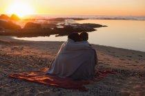 Пара романов на пляже на закате — стоковое фото
