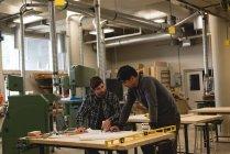 Два ремісників, обговорюючи над концепцією в майстерні — стокове фото