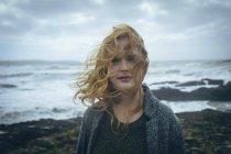 Портрет рыжей женщины, стоящей на ветреном пляже . — стоковое фото
