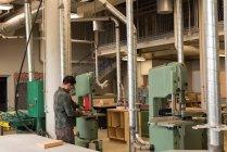 Вид збоку майстер роботи з машини в майстерні — стокове фото